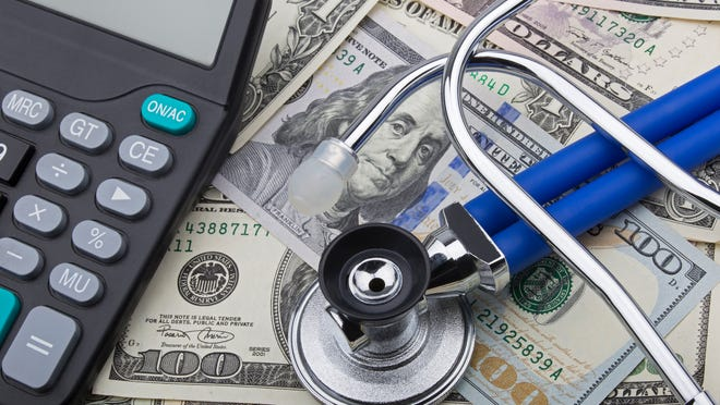 A stethoscope and calculator lying on top of hundred-dollar bills.