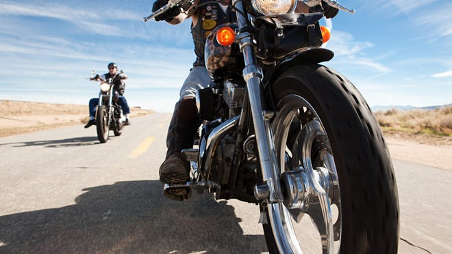 Two motorcycle riders on the highway in the desert.