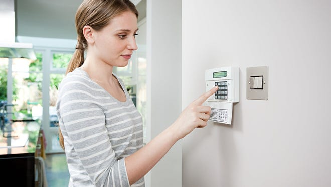 A woman setting the burglar alarm at her house.