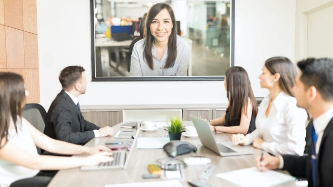 A conference room of business people video conferencing with a woman on a TV