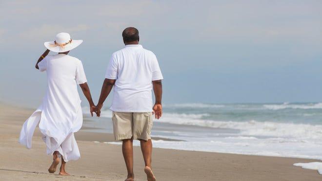 A man and a woman holding hands walking along a sandy beach.