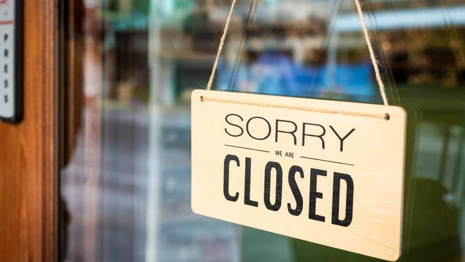 """A """"sorry we are closed"""" sign hangs on a door."""