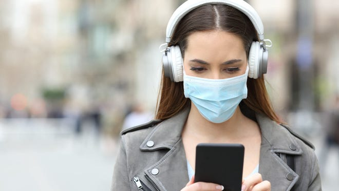 A young woman walking down an empty street, holding a smartphone while wearing headphones and a surgical mask.