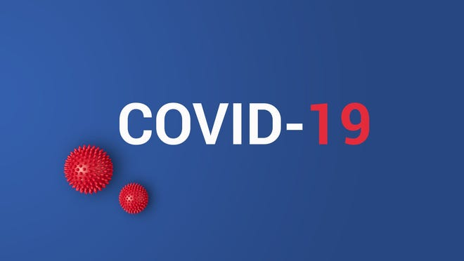 COVID-19 printed against blue background with red plastic balls representing the coronavirus