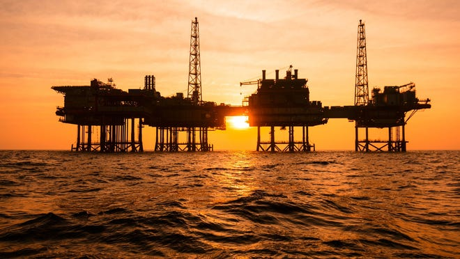 Offshore oil rigs at sunset.