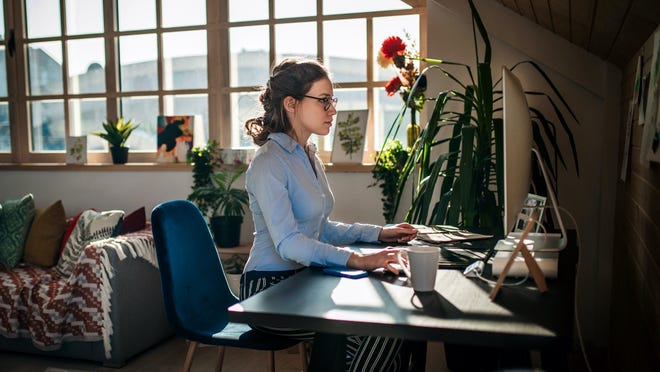Woman working at computer in her living room