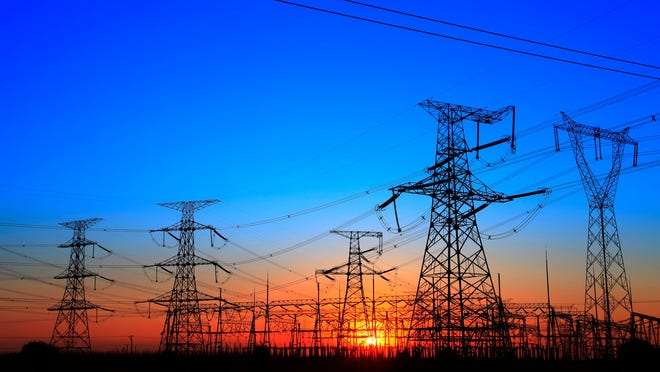 Power lines and towers at sunset or sunrise.
