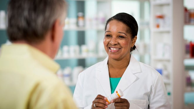 A pharmacist holding a prescription bottle while consulting with a customer.