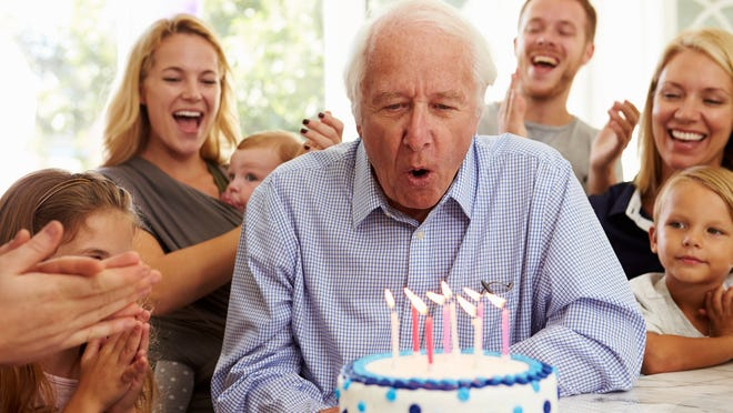 Older person blowing out candles on cake while family members clap and look on in the background.