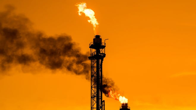 Flames and smoke are emitted from the top of an oil refinery's chimneys.