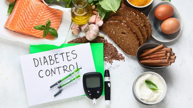 """A table with fresh, healthy foods, a glucose monitor, and card that reads """"Diabetes Control."""""""