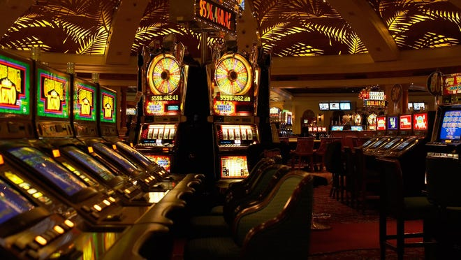 A casino empty of customers, with slot machines and other devices lit up.