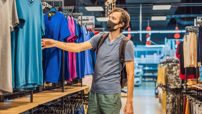 Masked man wearing a backpack and browsing through T-shirts in a clothing store