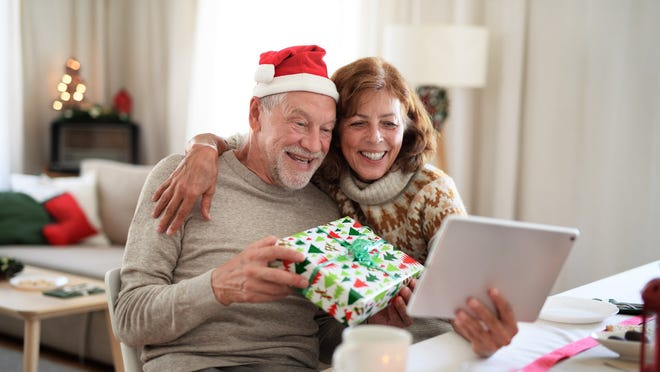 An older couple open a Christmas present while on a video call.