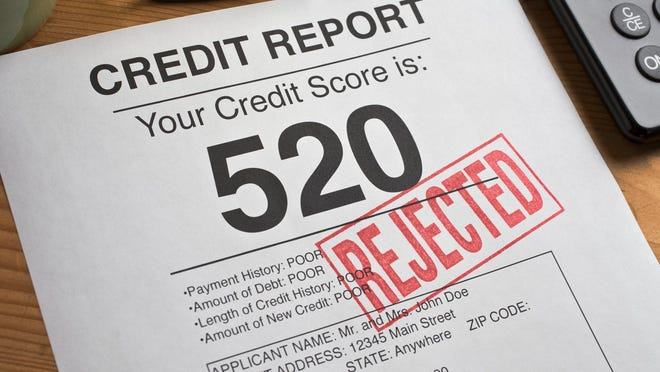 A credit report with a credit score of 520 in big print and the word rejected is stamped across it in red.