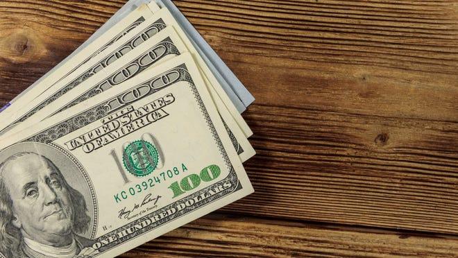 Pile of $100 bills on a wooden desk.