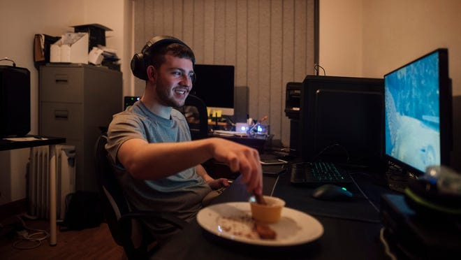 A young male gamer looking at a computer screen and smiling while dipping a piece of fried chicken into a container of sauce.