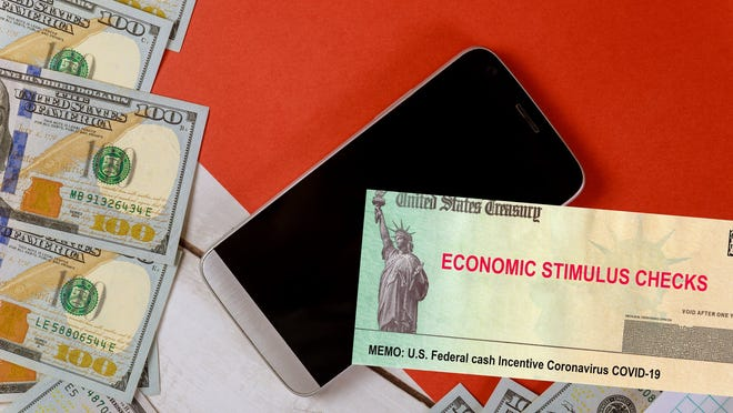 Economic stimulus check next to smartphone and $100 bills