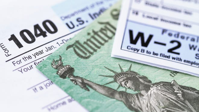 IRS tax forms with tax refund check.