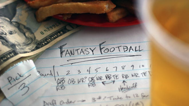 A piece of paper with fantasy football notes, sitting under a plate of french fries and a beer.