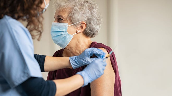 A health professional administers a COVID-19 vaccine to a lady.