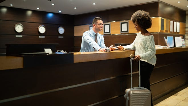 A woman checking into a hotel.