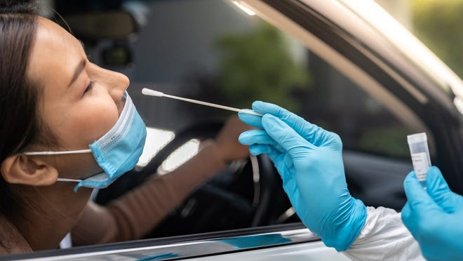 A woman wearing a surgical mask in a passenger seat getting a drive-thru COVID swab test from a clinician in gloves.