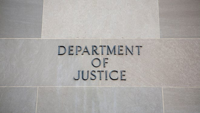 Department of Justice sign on a wall.