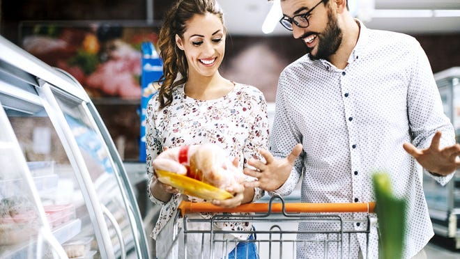 A couple looking at a frozen chicken in a supermarket.