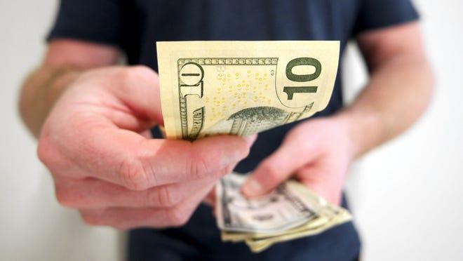 Man handing out a $10 bill