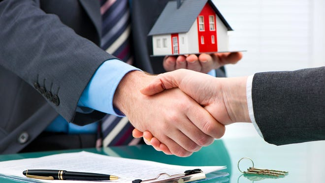 Two businessmen in suits shaking hands, with one holding a miniature house in his left hand.