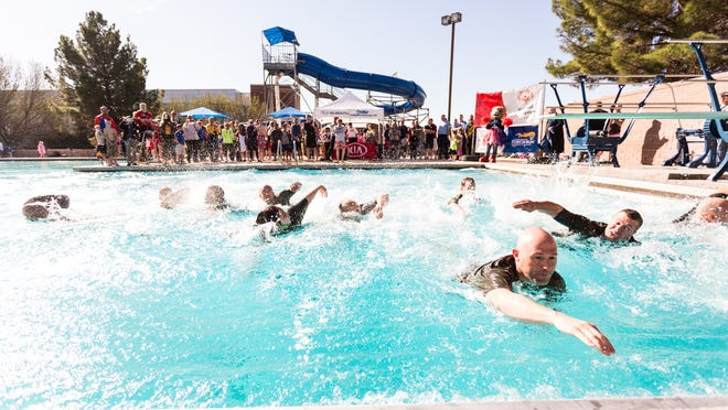 """Members of the St. George SWAT team swim to the edge of the pool after they """"took the plunge"""" as part of the annual Polar Plunge benefiting the Utah Special Olympics Saturday, Feb. 21, 2015."""