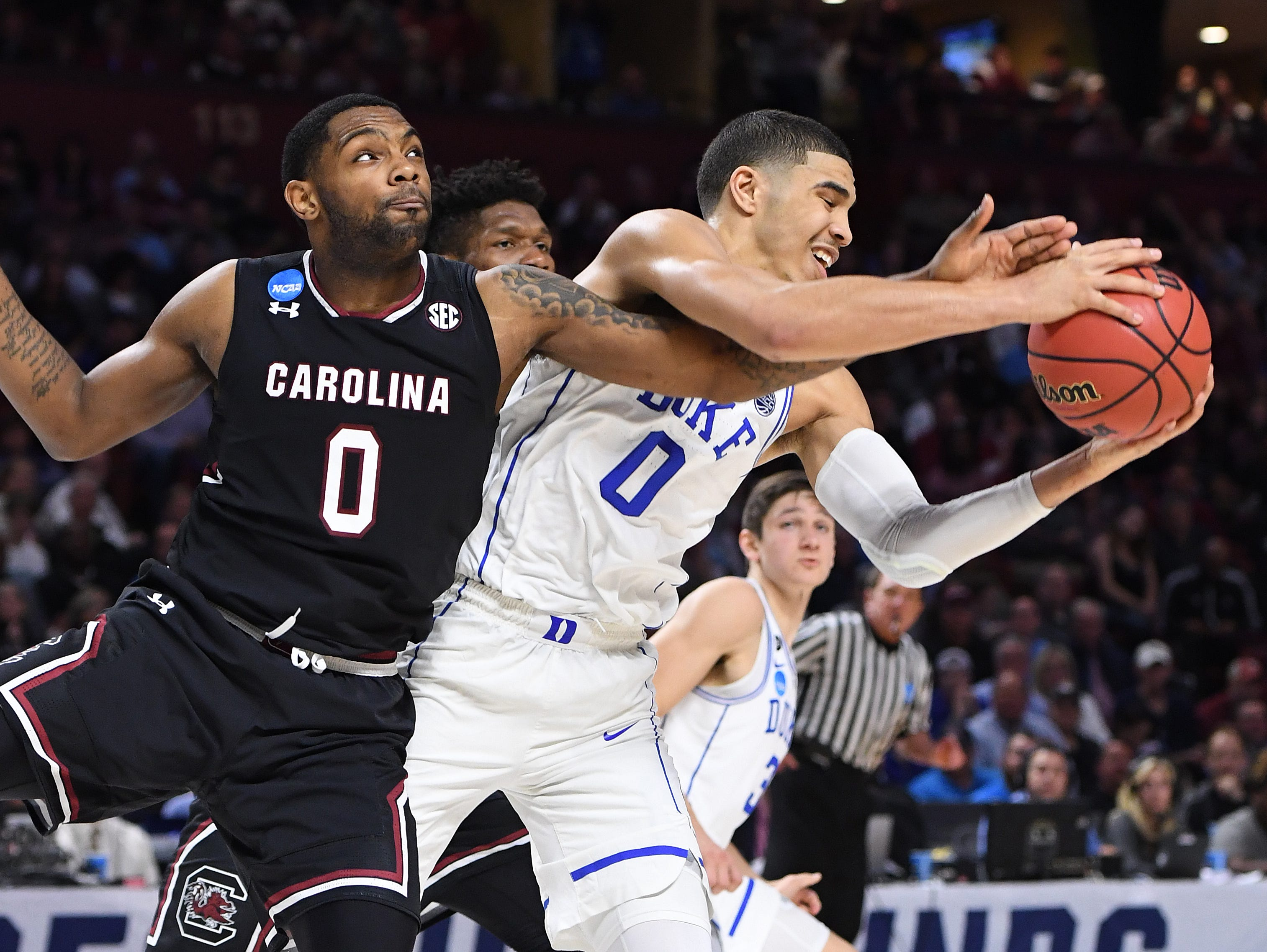 Duke forward Jayson Tatum (0) pulls down a rebound past South Carolina guard Sindarius Thornwell (0) during the 2nd round of the NCAA Tournament at Bon Secours Wellness Arena in downtown Greenville on Sunday, March 19, 2017.