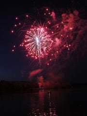 Fireworks reflect off the surface of the Cumberland