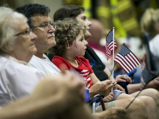 Kaylin Brandt, 5, holds an American flag during a Flag Day ceremony Sunday at Fire Station 1 in Lebanon. Also pictured, from left, are Charlotte Laudermilch, George Wilkins, and Lisa Brandt. The annual ceremony was moved indoors because of heavy storms that passed through the area.