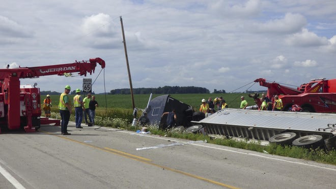 Crews work to extricate victims of a two-vehicle crash, Friday, Aug. 12, 2016 in Henry County, Ohio. A woman was killed and five people critically injured Friday morning after a van carrying members of an Ohio girls high school water polo team was struck by a semitrailer in northwest Ohio.
