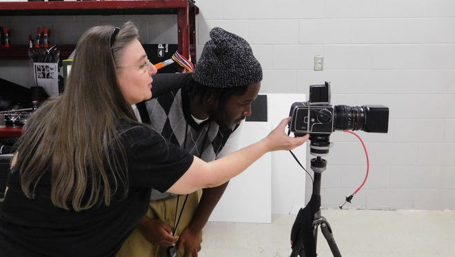 Daisean Brown and instructor Darlene Almeda set up a shot in the Lively photography studio.