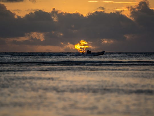 A boat floats in front of the setting sun at Rick's Reef on June 9.
