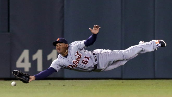 Detroit Tigers center fielder Ezequiel Carrera makes a futile attempt for a grounder as Minnesota Twins' Kurt Suzuki doubles to send in the tying run in the ninth inning of a baseball game, Tuesday, Sept. 16, 2014, in Minneapolis. The Twins won 4-3 with a walk-off single by Aaron Hicks.