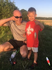 Tyler Wheeler, pictured here with his son, Landon, has enjoyed one fishing trip since returning home in mid-February. Many of his favorite activities, such as hunting, running and riding four-wheelers, remain off-limits until a portion of his skull is replaced in his next surgery.