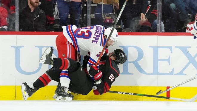 Rangers left wing Phillip Di Giuseppe (33) checks Carolina Hurricanes center Martin Necas (88) during a regular-season game. The two teams are slated to meet in NHL's 24-team tournament format proposed Tuesday [James Guillory/USA TODAY Sports)