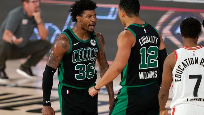 Boston Celtics' Marcus Smart (36) celebrates with Grant Williams (12) after sinking a basket and drawing a foul in the second half of an NBA conference semifinal playoff basketball game as Toronto Raptors' Kyle Lowry looks on Tuesday, Sept. 1, 2020, in Lake Buena Vista, Fla.