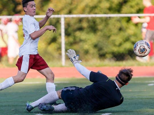 Highland Park's CJ Sanchez (2), left, lifts the ball over Bishop Ahr goalkeeper Daniel Cardona to score at Highland Park boys soccer on October 17, 2016.
