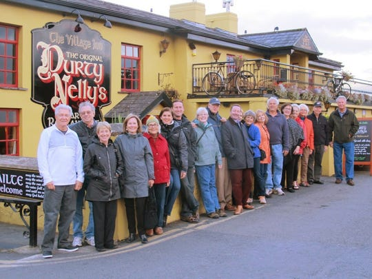 A group touring Ireland with Real Irish Travel poses for a photo in front of Durty Nelly's Pub in  Bunratty.