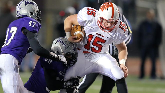 Center Grove running back Max Norris tries to shake a tackle from Ben Davis defensive lineman Antonio McEwen in the first half of the IHSAA Semi-State game held at Ben Davis High School on Friday, Nov. 14, 2014.