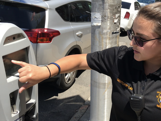 Briana Senatore, a Palisades Park traffic officer, demonstrates how to use the borough's camera-equipped parking meters on Broad Avenue on Thursday, June 14, 2018.