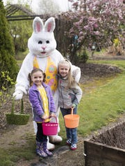 Hailey and Madison Vinogradoff are greeted by the Easter Bunny during the Bauman Farms Easter Egg hunt.