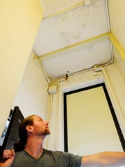 Chris Witmer, custodian at Stamm Elementary, shows the disrepair of the school ceiling.