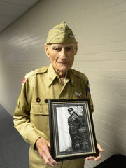 Jim McGrady, 98, of Fremont, who was the county's oldest living World War II veteran, holds a picture of himself from 1938. He served in the infantry from 1936 to 1939. McGrady died Thursday.