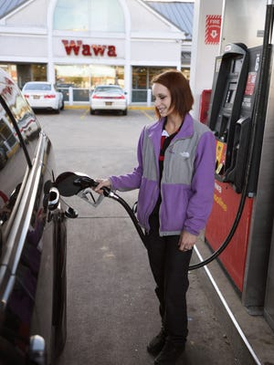 Kimberly Marshall, of Dagsboro, pumps gas at the Millsboro Wawa earlier this month. Gas prices are set to rise after OPEC agreed to cut production.